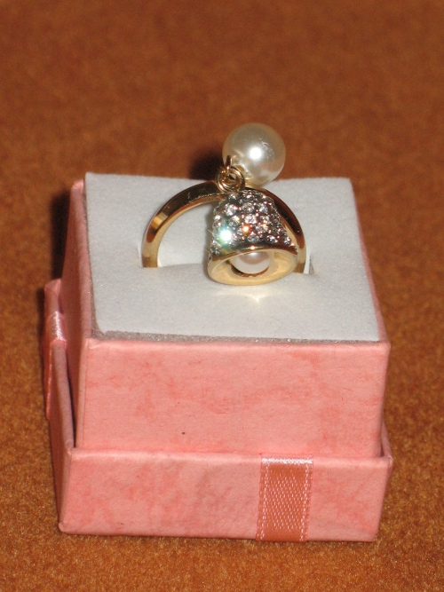 A gold ring with a bell decorated with Swarovski crystals and a pearl.